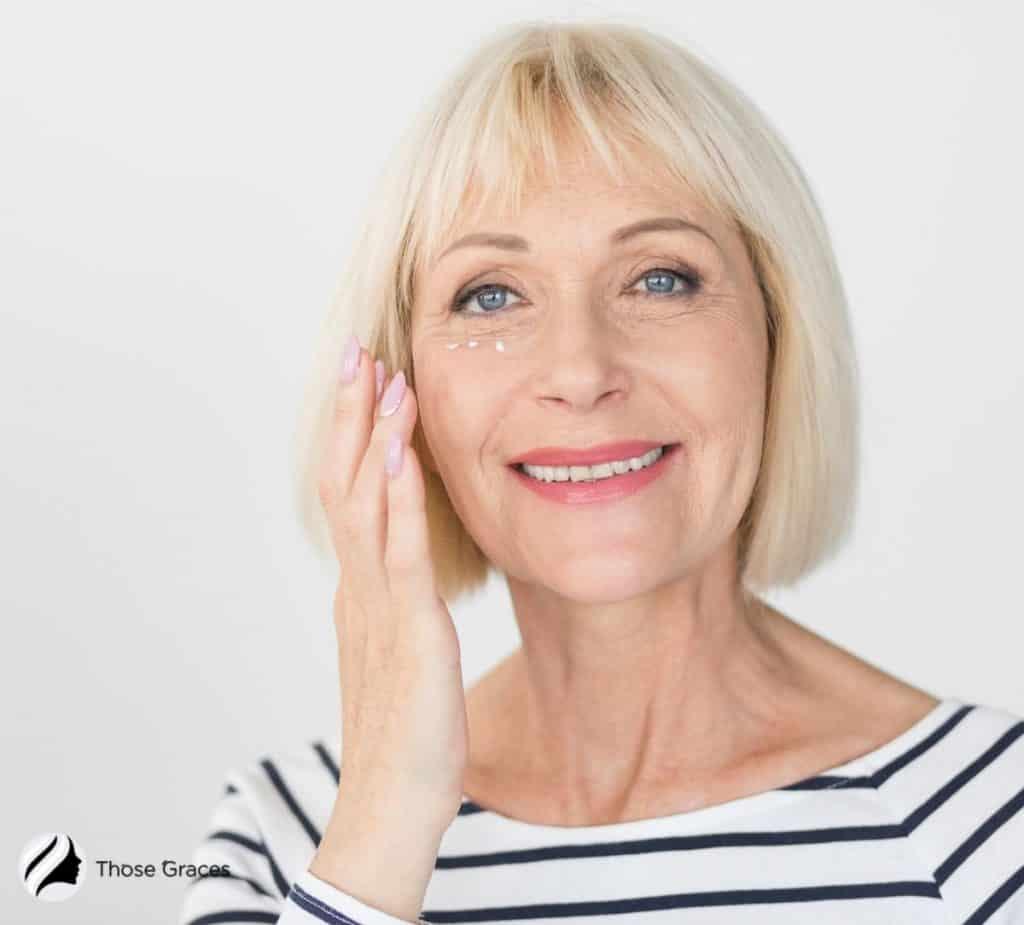 a blonde senior woman applying anti-wrinkle cream on her undereye
