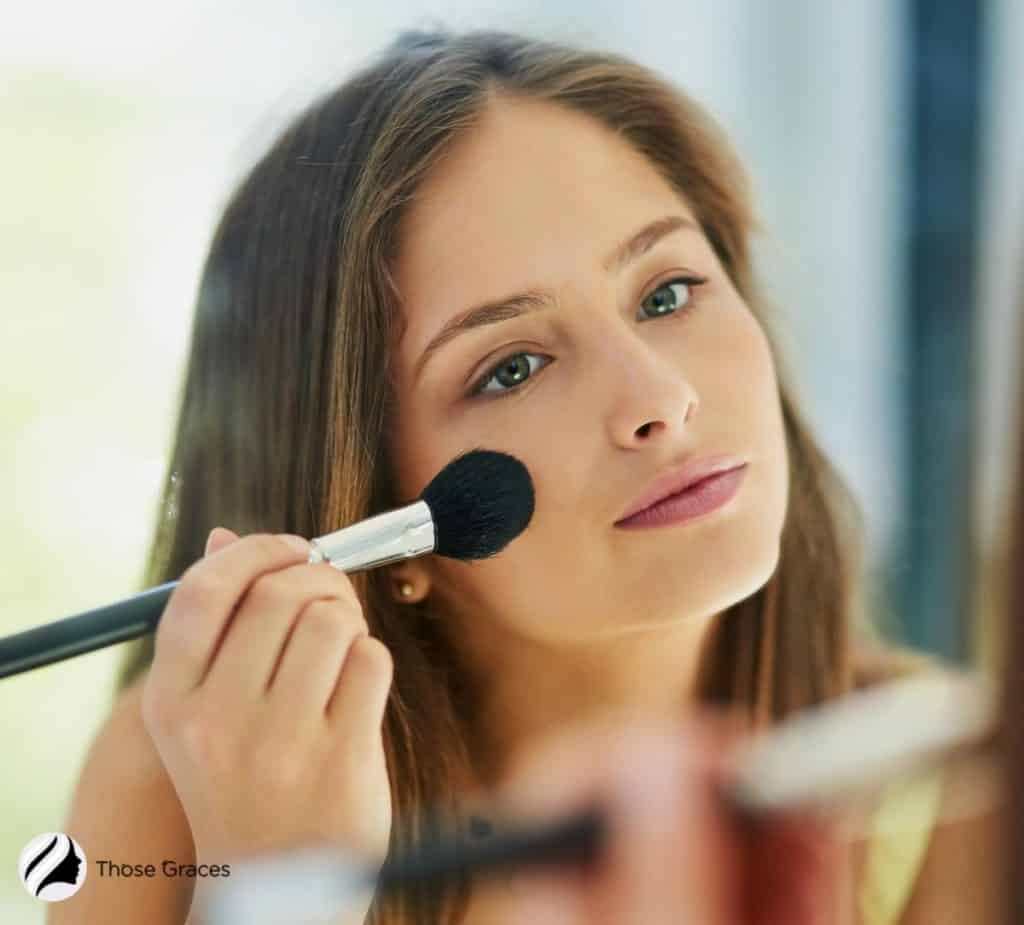 a pretty woman blending the makeup primer on her face using a brush