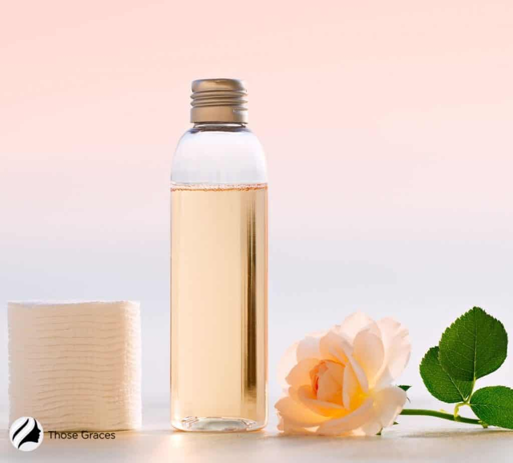 essence in a bottle with rose and cotton pads beside it