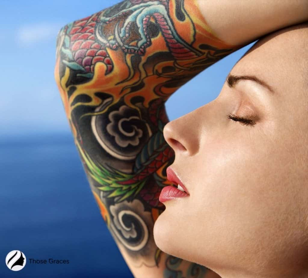 close-up shot of a lady's face and shoulder with colorful tattoos