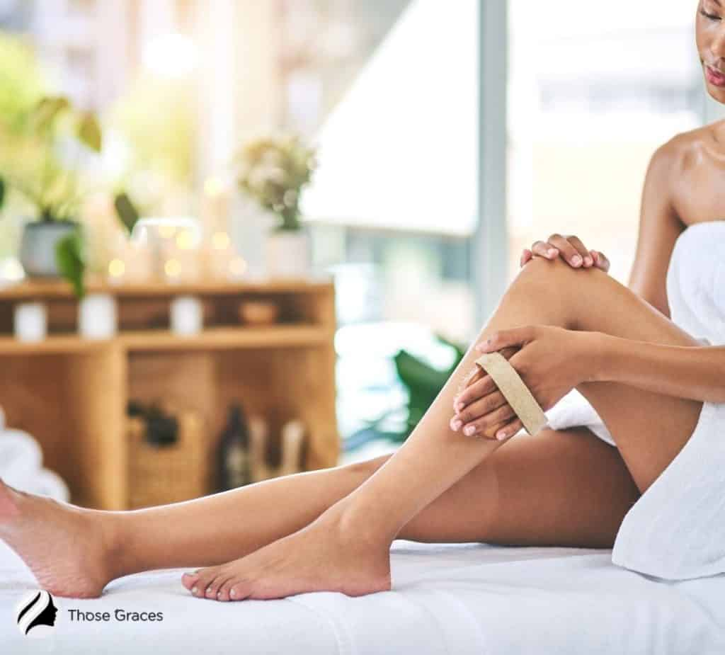 a lady exfoliating her legs before tanning them