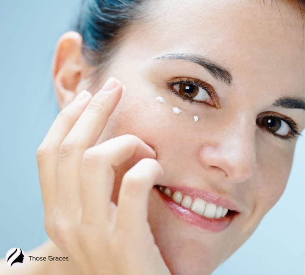 a smiling woman with eye creams on her under eye
