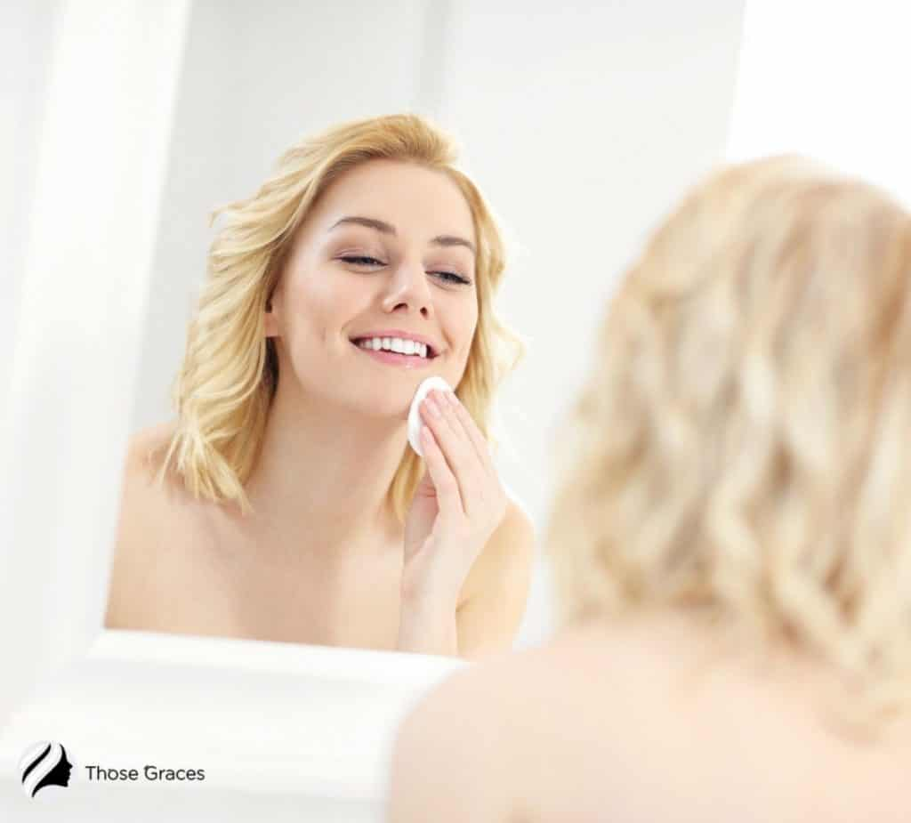 a blonde woman cleaning her face with a cotton pad