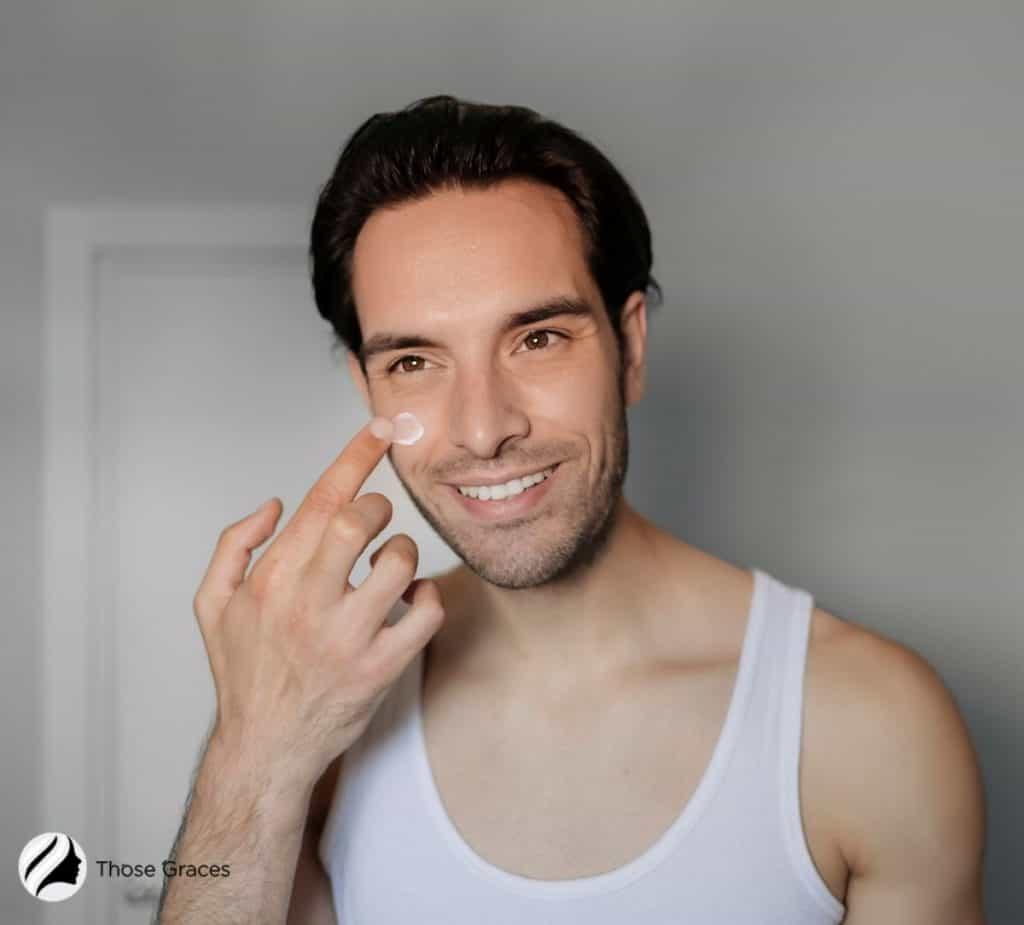 handsome man putting moisturizer on her cheek