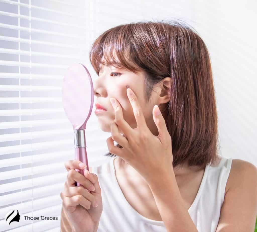 Korean lady looking at the pink handy mirror