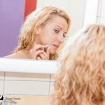 blonde curly girl checking her acne at the mirror