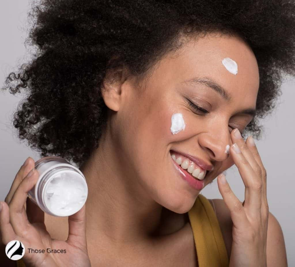 pretty curly-haired lady putting moisturizing cream on her face