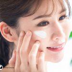 Korean girl demonstrating how to apply moisturizer on face