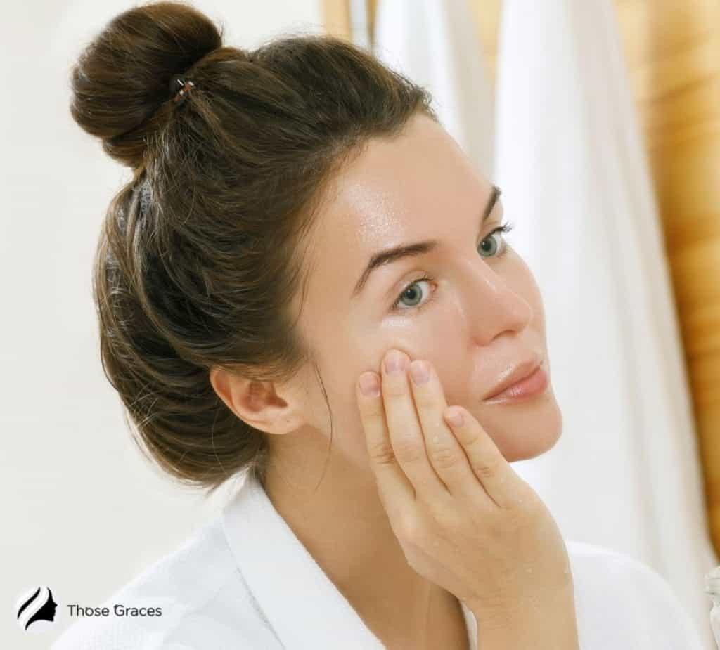 pretty woman in a bun cleansing face using oil