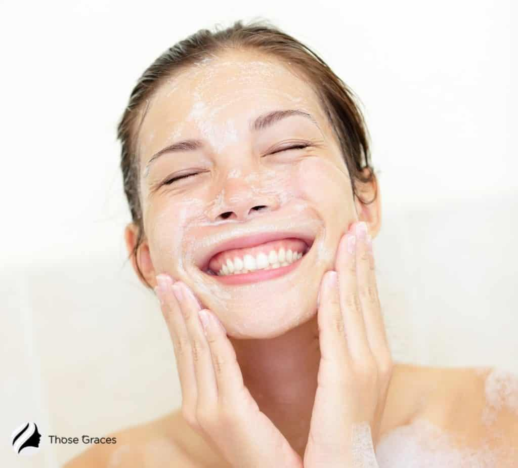 smiling woman cleansing face